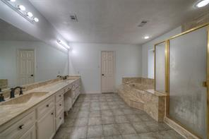 Master bath with double sinks, vanity area, large soaking tub and separate shower.