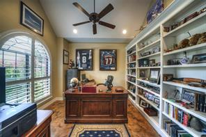 Office features stained concrete floors, built-in book shelves, and plantation shutters