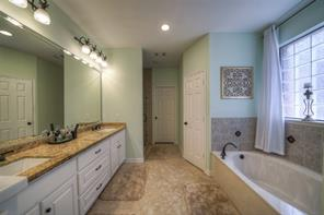 Master bathroom features granite countertops, his and her closets, and garden tub.