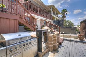 Outdoor kitchen with grill, smoker and wood-fired pizza oven.