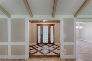Perfect entrance hall has custom tile work , wrought iron chandelier and faux coppered ceiling.