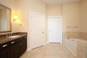 Tranquil master bath features tile floors & granite counters, dual vanities, frameless walk-in shower, soaking tub & private water closet