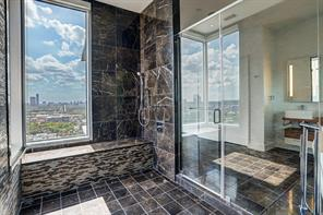 Luxurious touches and amenities embellish  the spectacular master bath graced by stunning brown marble floor and wall mounted electric towel warmers.