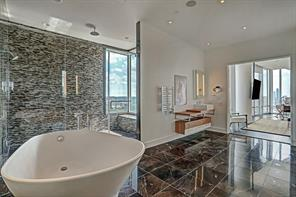 Spectacular over- sized shower boasts wall shower head, rainfall shower and bench.