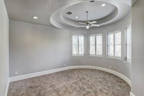 Game room - vaulted ceiling, windows with plantation shutters, built-in bench, recessed lighting, ceiling fan, carpeted floor. Adjacent half bath.