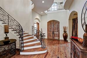 Inviting two-story foyer with cypress wood double doors and wrought iron hardware. 28' ceiling.