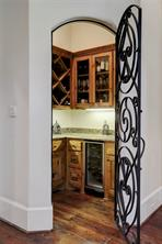 Wine Room - wrought iron door, glass front cabinets, bar sink, built-in wine cooler and wine rack.