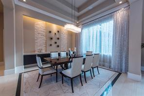 The dining room is enhanced by stone walls, floating cabinets, recessed lighting and raised ceiling with sheer and black-out draperies.