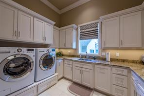 Downstairs utility room with raised full-size washer and dryer and tons of storage.