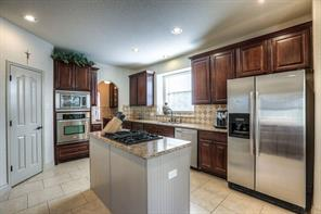 Kitchen features granite, pantry, island w/gas stove top.