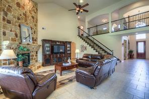 The living area has a floor-to-ceiling stone fireplace with stone mantel. The tile flooring is very neutral. High ceilings keep this room light and airy, and you can put your touch on the colors and decor to make it your own.