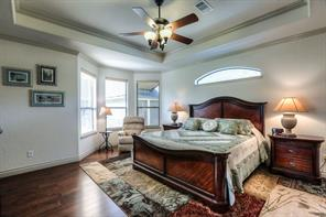 Main master suite has wood floors, crown molding, tray ceiling, ceiling fan and entry to the back porch.