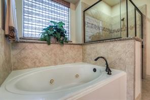 Whirlpool tub and oil-rubbed bronze fixtures and an enormous closet complete with mirror round out the master bath.