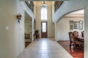 Two-story entrance with arches and windows for plenty of natural light. Wood floors in dining and study.