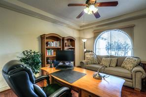Spacious study has a view to the front, crown molding, tray ceiling, ceiling fan.
