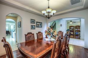 Formal dining has great flow for entertaining, through butler's pantry and into main living room area. Note the tray ceiling and wood floors, archways to other rooms.