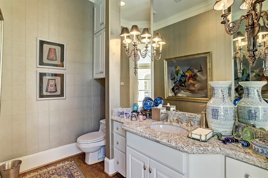 The formal POWDER ROOM is just off the Front Entry and features an elegant granite slab counter top/backsplash with painted cabinets below, undermount sink with decorative fixtures, crown/base molding, recessed lighting, decorative sconces placed on a mirrored wall, papered walls and built-in storage cabinet.