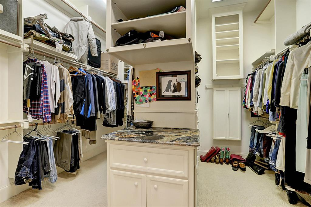 The spacious MASTER CLOSET features carpeted flooring, built-in packing station with slab granite counter/ painted cabinet and drawers below and shelving above, hanging rods, built-in shelving and jewelry cabinet.