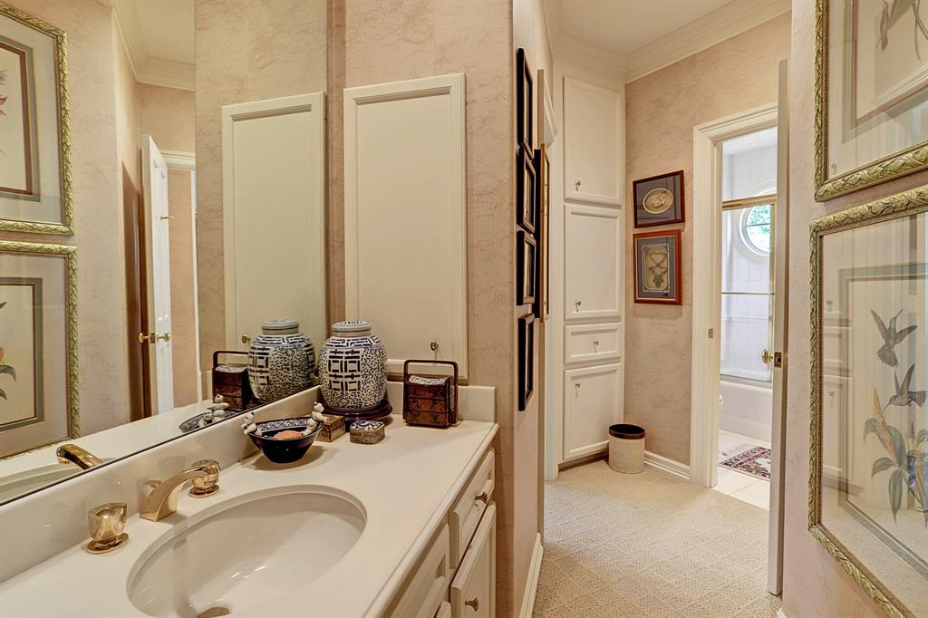 The SHARED/HOLLYWOOD BATH between two guest bedrooms includes built-in medicine cabinet. painted walls, crown/base molding, tub/shower with tile surround, dual sink areas.