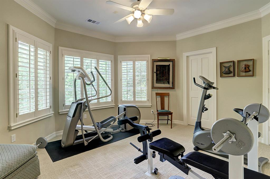 The second upstairs GUEST BEDROOM/EXERCISE ROOM (15 X 12) features carpeted flooring, ceiling fan, painted walls, walk-in closet with drawers/shelving and shuttered windows in a bay formation.