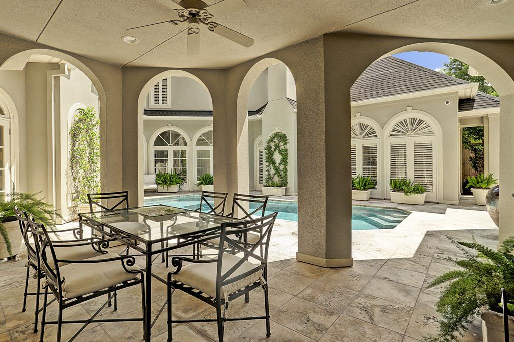 Adjacent to the pool is the PAVILLION with its stucco columns and arched openings which delineate the space and provides a covered space for the Bar and table with chairs. The tile flooring is easy to maintain and the centrally placed ceiling fan allows further breeze and comfort from warm weather temperatures.