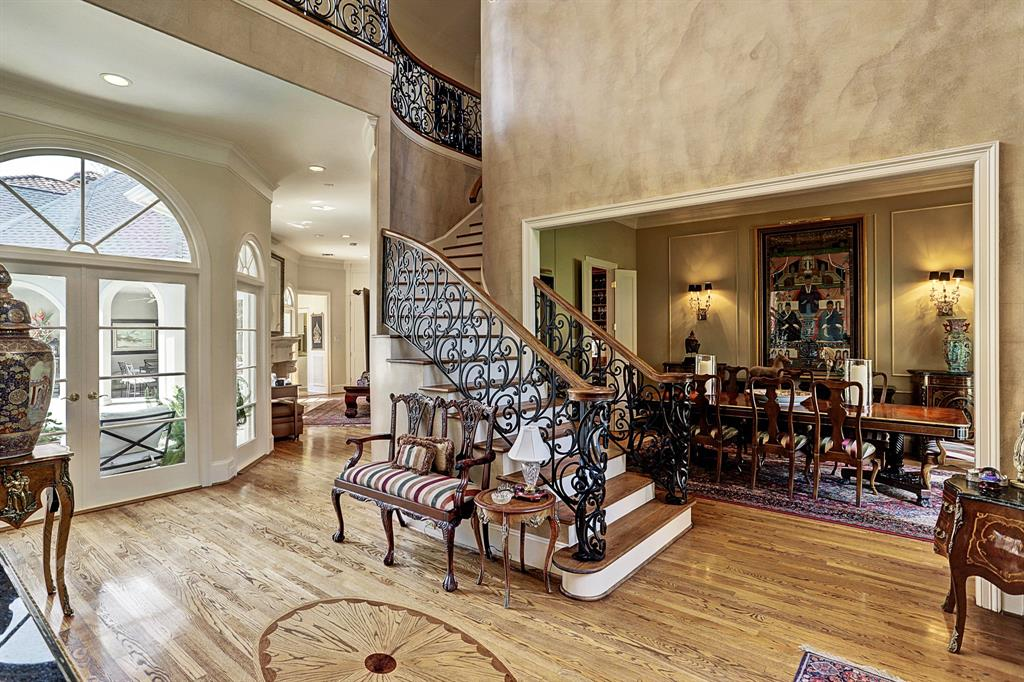 The open spatial ambiance of the FRONT ENTRY allows an easy flow from the Entry to the adjacent Dining and Living areas with a corridor leading to the less formal Family Room and Kitchen areas. The centrally located staircase is impressive with its graceful curved outline, wrought iron detailing, wood treads/painted risers.
