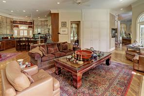 The FAMILY ROOM includes oak flooring, gas log fireplace with stone surround/mantle, crown/base molding, door to outdoor covered area and pool, hidden entertainment center, built-in desk closet with granite slab counter/shelving.