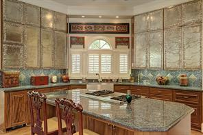 The KITCHEN AND BREAKFAST AREA is spacious in size (16 X 24).  The KITCHEN includes additional seating and storage/counter space with its central island.  The island's slab granite is repeated on additional stained cabinets. Striking hand-forged, silver plated copper cabinets flank the corner shuttered windows above the stainless Farmer sink with fixtures. Also noteworthy are the walk-in pantry, under-cabinet lighting, recessed lighting and decorative back plash tiles.