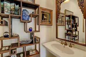 The second HALF BATH is located just off the Family Room/Kitchen area and near the two car garage and side door to the outdoor covered Bar. Tile flooring, pedestal sink with bronze fixtures, crown/base molding, recessed lighting and light fixtures are included in the space.