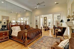 The first floor MASTER BEDROOM SUITE includes a centrally placed gas log fireplace with stone surround/mantel flanked by shuttered windows overlooking the backyard pool/spa/covered patio, mirrored wall, ceiling fan, recessed lighting and sliding glass doors opening to the adjacent Study.