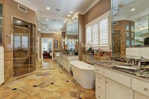 The luxurious MASTER BATH features marble tile flooring with decorative inserts,  mirrored walls, separate water closet with linen cabinet, marble slab counters/backsplash, painted cabinets, dual Kohler undermount sinks, freestanding soaking tub with marble surround, shuttered window, glass front walk-in shower with two rain heads/marble slab surround/built-in bench and master closet.