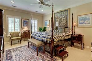 One of four GUEST BEDROOMS - this one (17 X 15) includes carpeted flooring, painted walls, crown/base molding, ceiling fan, shuttered windows, walk-in closet and shared bath with an adjoining guest bedroom.
