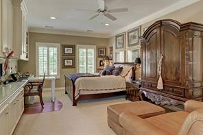The spacious GUEST BEDROOM #3 (22 X 18) includes a double door entry, built-in desk/cabinets/shelving, shuttered windows,  painted walls, ceiling fan, recessed lighting, carpeted flooring, walk-in closet and en suite bath.
