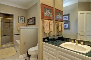 The EN SUITE BATH features tile flooring with decorative inserts, green tile counter top and backsplash, crown/base molding, built-in speakers, painted cabinets/drawers, recessed lighting, Kohler tub with tile surround, glass front shower with built-in bench and tile surround.