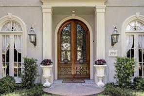 The stately front façade is handsomely and classicly finished with a central wood/glass/wrought iron double door flanked by stucco pilasters and mullioned windows on the first two floors and dormer windows on the third floor.