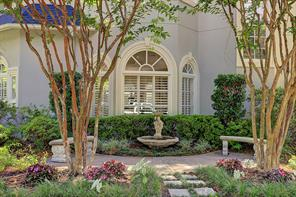 A closer view of the charming garden with fountain and benches on the house's west side.  The space is delicately landscaped to create a peaceful spot and which can also be viewed from the home's interior Breakfast Area.