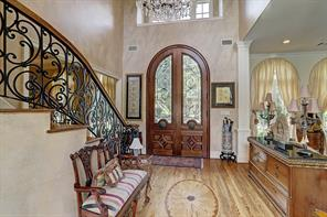 The two story FRONT FOYER includes a notable crystal chandelier, wood flooring with central decorative wood detailing, stenciled walls, second floor mullioned window and Mahogany double door with decorative wood carved detailing and wrought iron accents.