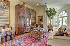The formal LIVING ROOM (17 X 13) includes oak flooring, flooring to ceiling arched windows, built-in storage cabinets, crown/base molding, recessed lighting, built-in speakers, painted walls with painted wood trim.
