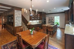Breakfast room and kitchen with granite countertops, electric cooktop, built in Subzero refrigerator freezer, double ovens, warming drawer, and access to the back staircase.  Back service hallway, with door to porte cochere, utility room with sink and additional storage, and half bath.