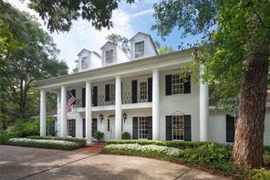 Gracious two story entry with marble floors, sweeping staircase and chrystal chandelier, with entry to formals, family room, master suite hallway and wet bar.