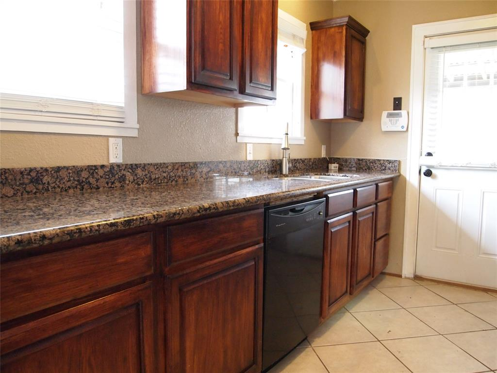 Kitchen features granite counter tops and lots of storage.