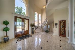 The entry is impressive with the marble flooring and winding staircase.