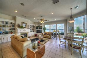 The family room has tile flooring and a gas log fireplace flanked by bookcases and entertainment center.