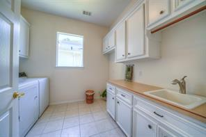 The laundry room has lots of cabinets and a space for an additional fridge or freezer.
