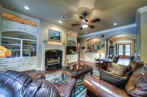 Cozy family room has a wood-burning fireplace with gas connections, ambiance lighting above the cabinets and built-ins for storage. Also, note the wood flooring, crown molding and there is a wet bar.