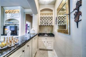 WEt bar is complete with wine rack, cabinets for storage and of course, the sink.