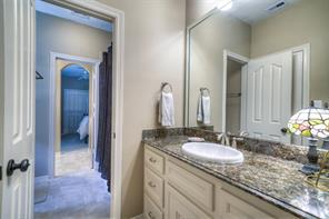 There is a jack-and-jill bathroom between two bedrooms that has white cabinetry with drawers.