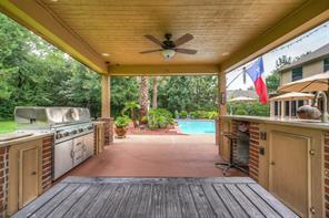 Outdoor kitchen space with large stainless grill, counter space and sink.