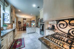 Fantastic kitchen has stainless appliances, 5-burner gas cook top w/hood, double oven, microwave and tons of counter space for food prep. The cabinets are beautiful with the faux antique glaze.