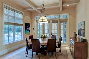 Breakfast room with wall of windows and French doors that open to the summer kitchen with sitting area.  The limestone floors and the bleached beams in the kitchen carry into the breakfast room. Builtin speakers are through out the main living areas.